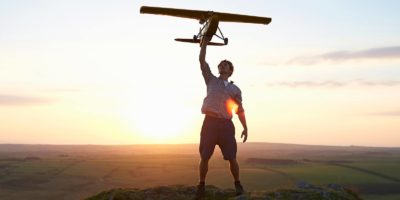 A man stands on the top of a rocky hillside and holds a model airplane above his head as the sun sets behind him.